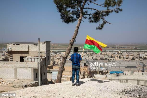 A boy seen standing on a hill in kobani and raising a Kurdish flag toward the Turkish flag on the other side An estimated 400000 refugees fleeing the...