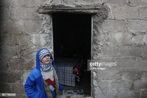 A boy seen wearing a scarf to keep him warm during the winter while passing next to an old shop Despite the ongoing conflict in Syria life in...