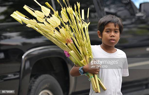 A boy sell palm branches in preparation for 'Palm Sunday' on a Manila sidewalk on April 4 2009 Lenten Sunday in this largely Roman Catholic nation...