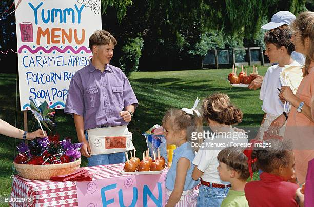 boy selling caramel apples - gala stock pictures, royalty-free photos & images