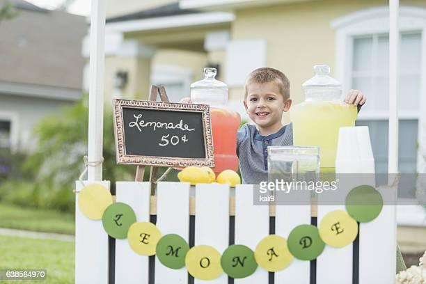 Boy selling lemonade in front yard