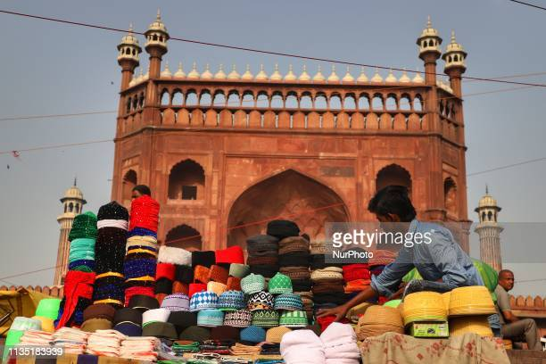 A boy selling skull caps waits for the customers outside Jama Masjid in the Old Quarters of Delhi