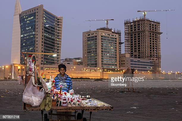 A boy sells decorations at a stall as the Harbour Front tower left and the under construction towers stand in the background in the Clifton area of...