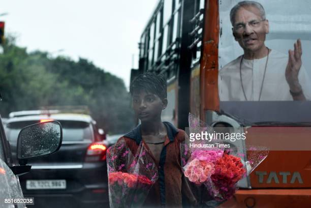 A boy sells flowers at a traffic signal during rainfall on September 22 2017 in New Delhi India DelhiNCR got some respite from the heat and humidity...