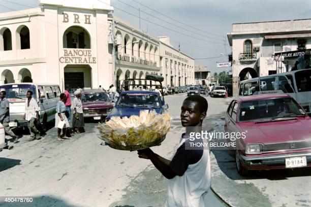 A boy sells fried bananas on June 15 1994 in front of the 'Banque de la République de Haiti' The economic crisis grows more serious as the tougher...