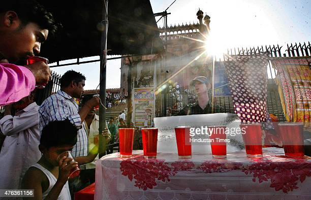 A boy sells Sharbat during a hot weather in front of Jama Masjid as heat wave conditions prevailed in Northern India as the mercury remained above 40...
