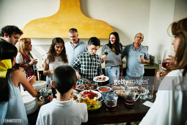 boy serving himself food in kitchen during multigenerational family party - sociale bijeenkomst stockfoto's en -beelden