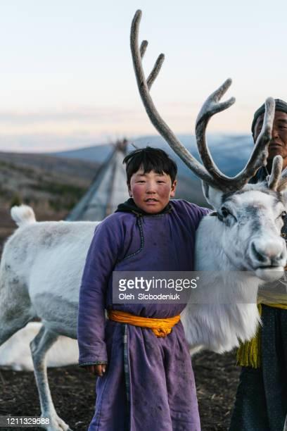 冬のモンゴルでトナカイを羊飼いする少年 - モンゴル ストックフォトと画像