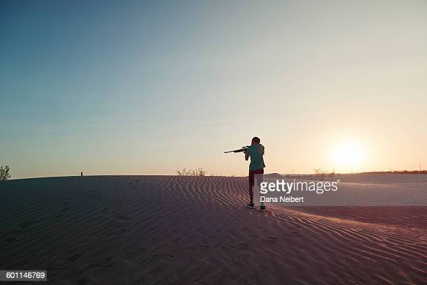 boy shooting a bb gun in the desert - dana barron stock photos and pictures