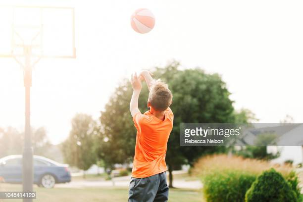 boy shooting a fadeaway jump shot - shooting baskets stock pictures, royalty-free photos & images