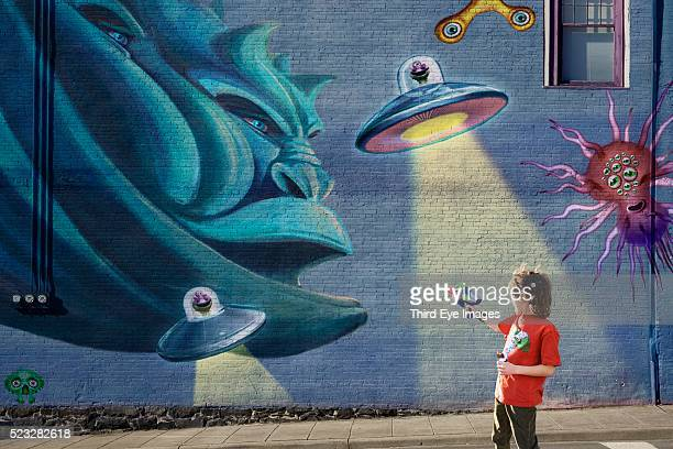 Boy shooting aliens painted on a wall