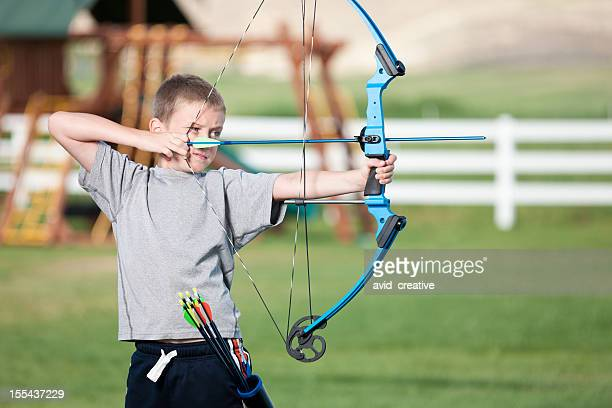 Boy Shooting Bow in Backyard