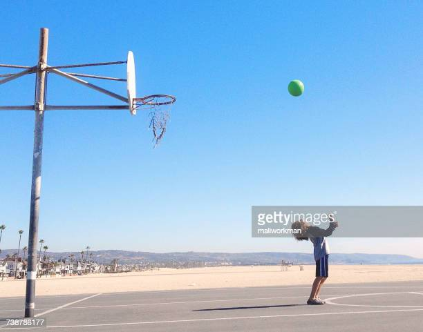Boy shooting hoops on basketball court, California, America, USA