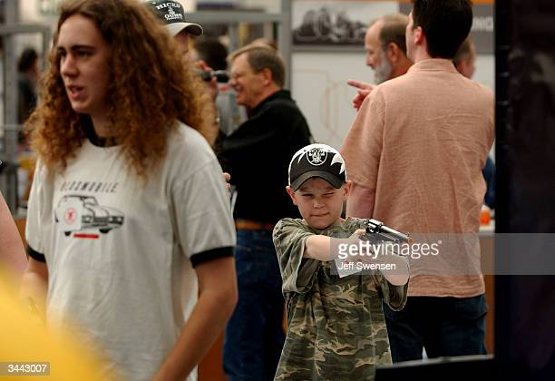 A boy shoots a laser pistol at a target in a booth at the 133rd Annual National Rifle Association Convention being held at the David L Lawrence...