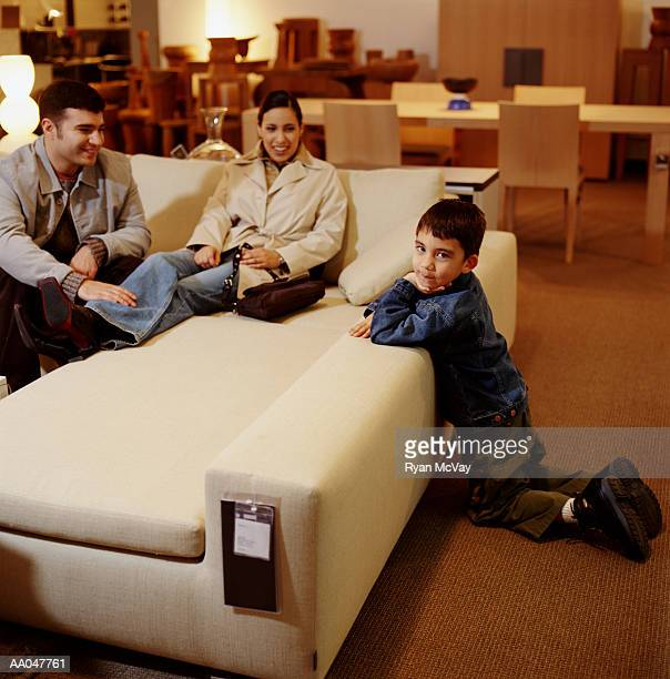 Boy (4-6) shopping for couch with parents