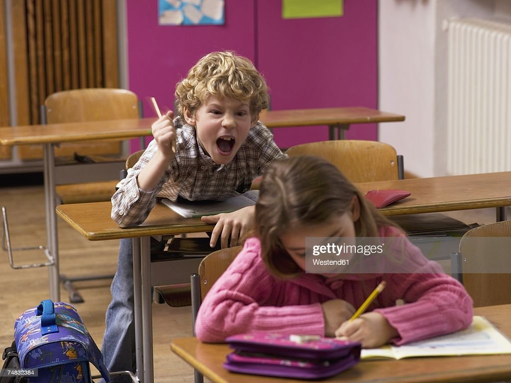 Boy (4-7) shouting behind girl in class room : Stock Photo