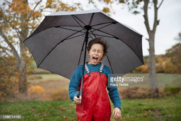 boy shouting with eyes closed holding umbrella - denmark stock pictures, royalty-free photos & images