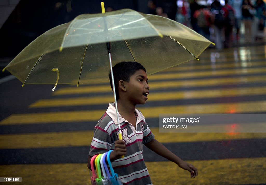 A boy shouts for customers as he sells umbrellas during a light rain outside a shopping mall in downtain Kuala Lumpur on January 4, 2013. Malaysia is heavily reliant on migrant workers: they number about 2.2 million people and are the mainstays of the plantation and manufacturing sectors. AFP PHOTO / Saeed Khan