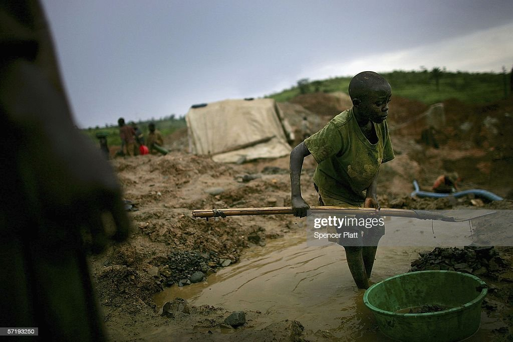 A boy shovels dirt into a bucket which will be sifted through while looking for gold March 27, 2006 in Mongbwalu, Congo. Thousands of Congolese scrape together meagre livings from mining. Gold and other mineral deposits, which are numerous in the volatile north-east of the country, have become a catalyst to much of the conflict in Congo. The Democratic Republic of Congo (DRC), a country that loses an estimated 1,400 people per day due to war since 1998, is struggling to hold Presidential elections this summer. The volatile East of the country, which is situated hundreds of miles from the capital Kinshasa, has been the focal point of continued violence. Numerous militias and warlords have vied for control of the mineral rich eastern Congo for decades, creating instability and continued bloodshed.