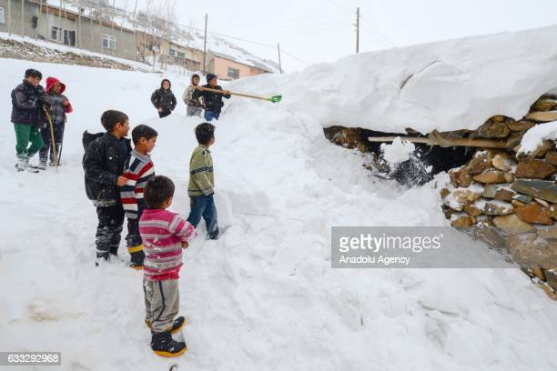 A boy shovels the snow outside a stone house as children watch him after heavy snowfall during winter season in Yukari Narlica village of Catak...