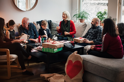 Boy showing Christmas presents to multi-generation family at living room - gettyimageskorea