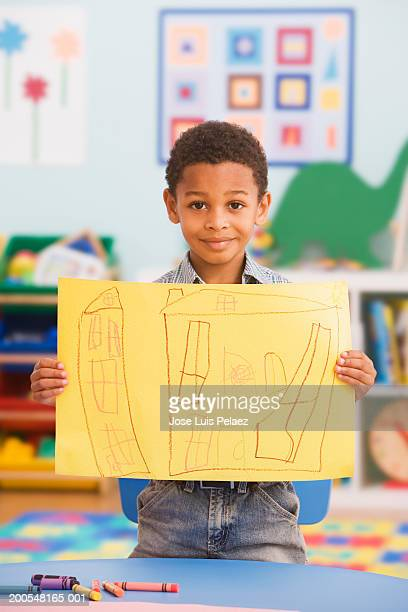 Boy (2-3) showing drawing in class, smiling, portrait