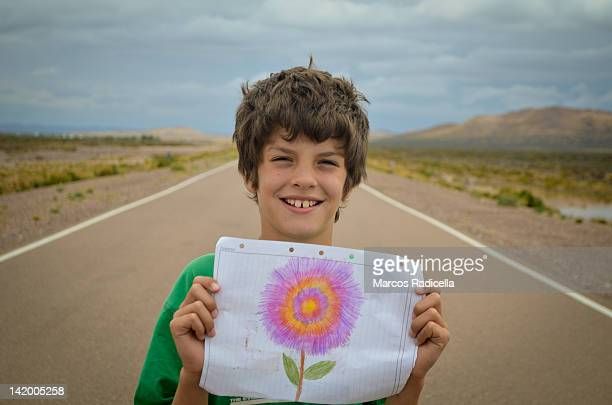 boy showing drawing with flower - radicella stock photos and pictures