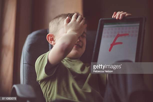 boy showing failing grade on electronic tablet - miss f fotografías e imágenes de stock