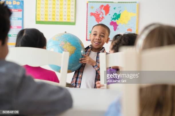 Boy showing globe to classroom