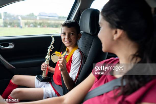 boy showing his soccer mom the trophy he won in summer camp - medallist stock pictures, royalty-free photos & images