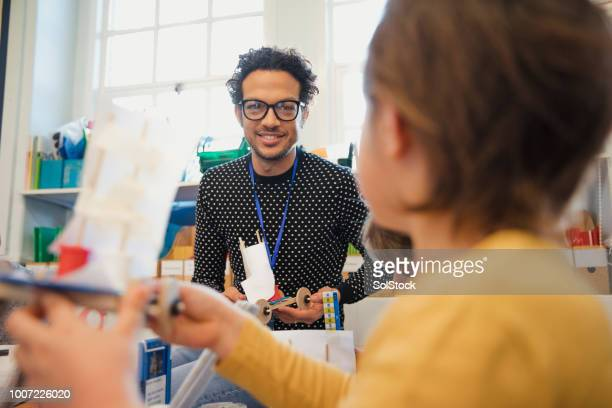 boy showing his teacher his work in elementary class - physics stock pictures, royalty-free photos & images