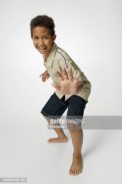 boy (8-9) showing karate pose in studio, portrait - ein junge allein stock-fotos und bilder