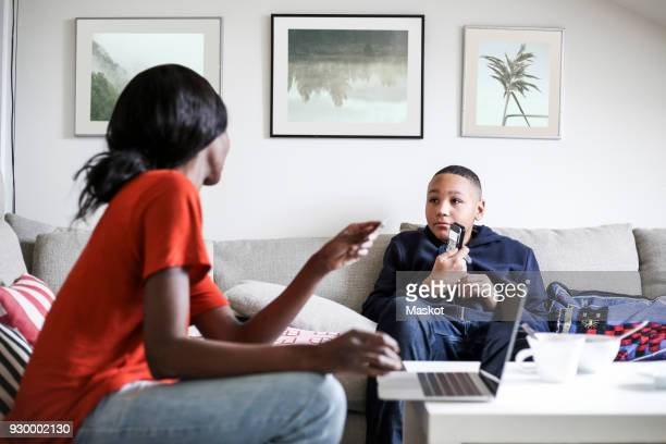 Boy showing mobile phone to mother with laptop and credit card in living room