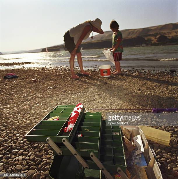 Boy (4-6) showing mother his catch (focus on tackle box)