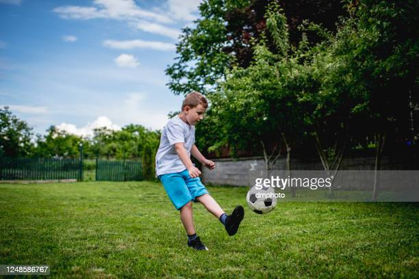 boy showing off his football skills in the backyard - play off stock pictures, royalty-free photos & images