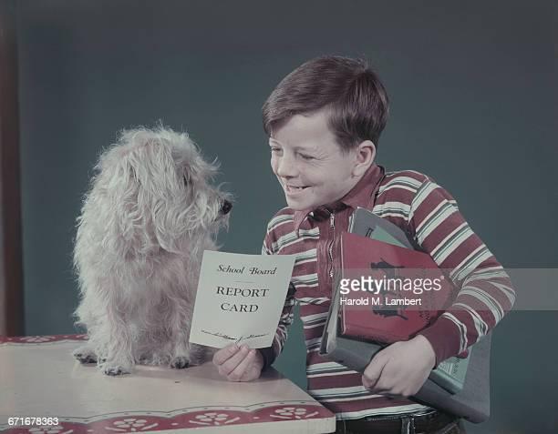 boy showing report card to dog  - westers schrift stockfoto's en -beelden