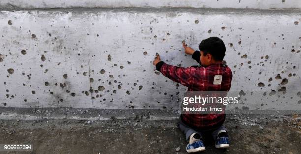 A boy showing splinters marks of mortar shell on a wall fired from the Pakistan side on January 18 2018 in Arnia district of Jammu India Indian...