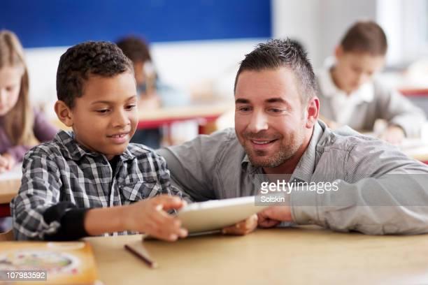 Boy showing teacher schoolwork on tablet computer