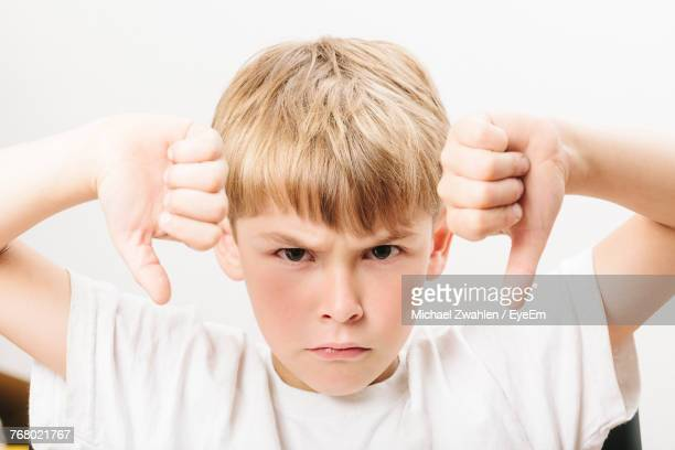 boy showing thumbs down over white background - weigeren stockfoto's en -beelden