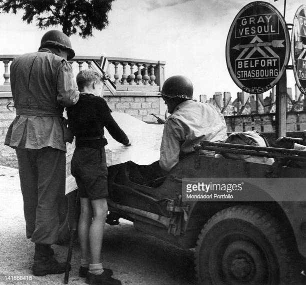 A boy showing two US soldiers the road to Strasbourg from Besancon on a map France September 1944