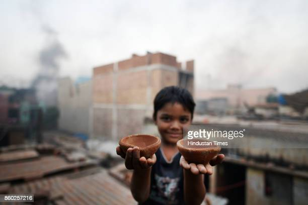 Boy shows earthen lamps as potters in West Delhi's Uttam Nagar are busy in making earthen diyas and other decorative items for the upcoming Diwali...