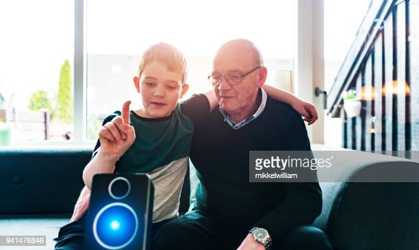 Boy shows grandparent how to use a digital assistant with voice commands