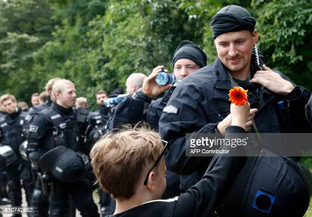 TOPSHOT A boy shows his appreciation for the police watching a demonstration pass by on July 8 2017 in Hamburg northern Germany as world leaders meet...