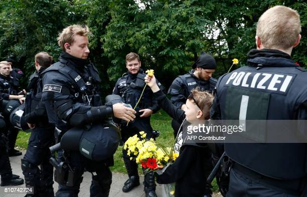 A boy shows his appreciation for the police watching a demonstration pass by on July 8 2017 in Hamburg northern Germany as world leaders meet during...