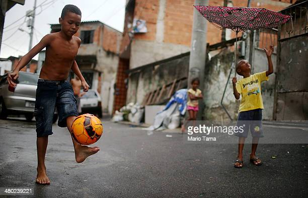 A boy shows off his soccer skills in the Complexo do Alemao pacified 'favela' community on March 23 2014 in Rio de Janeiro Brazil The 'favela' was...