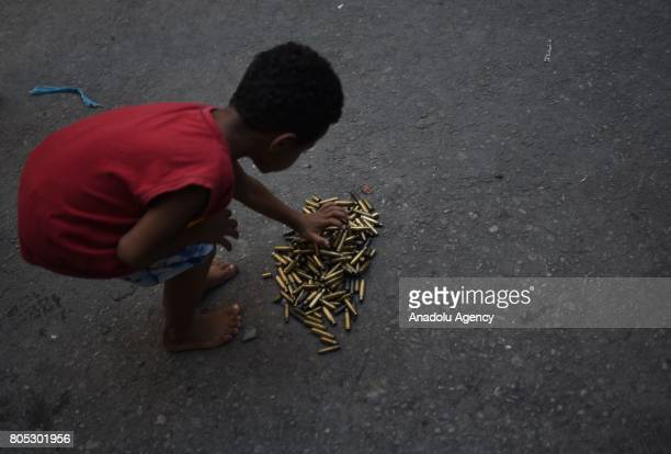 A boy shows spent bullet casings after a police operation at the Mangueira favela in Rio de Janeiro Brazil on June 30 2017