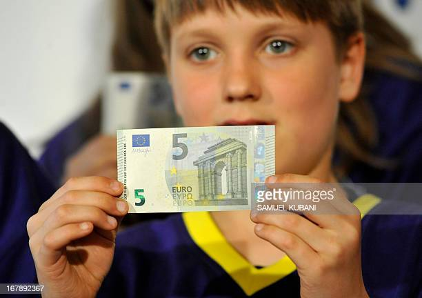 A boy shows the new fiveeuro banknote after it was presented by European Central Bank President during a press conference following the Governing...