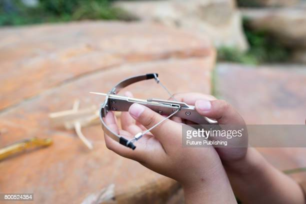A boy shows toothpick crossbow latest dangerous toy that parents called for banning on June 24 2017 in Yangzhou China The mini crossbow can shoot...