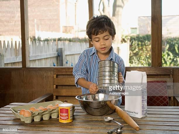 Boy sifting flour into bowl