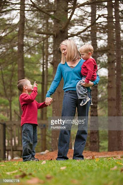 Boy signing the phrase 'I love You' in American Sign Language while communicating with his mother in a park